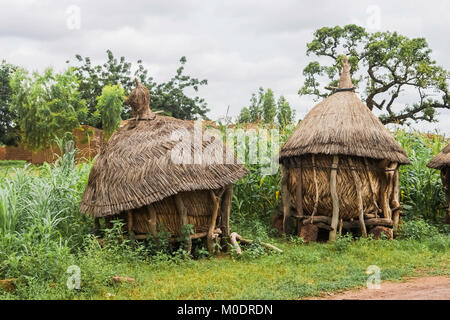 Two traditional african granaries made of wood and straw in a field of millet, Ouagadougou, Burkina Faso. - Stock Photo