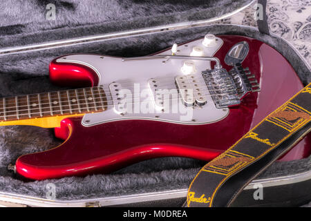 Fender Stratocaster (Strat). Classic electric guitar in its soft lined hard case with strap. Candy apple red paint finish with Floyd Rose tremelo. Stock Photo