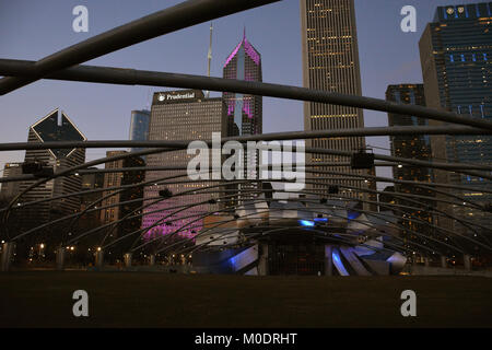 The Pritzker Pavilion in Chicago's Millennium Park is illuminated against the skyline on a winter evening. - Stock Photo