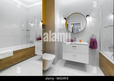 Modern bathroom with oval mirror in stylish apartment - Stock Photo