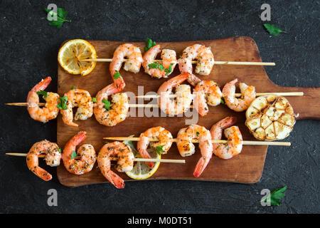 Grilled shrimp skewers. Seafood, shelfish. Shrimps Prawns skewers with herbs, garlic and lemon on black stone background, - Stock Photo