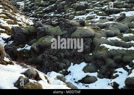 A lava field on the Southern Coast of Iceland with snow, ice, rocks and moss. - Stock Photo
