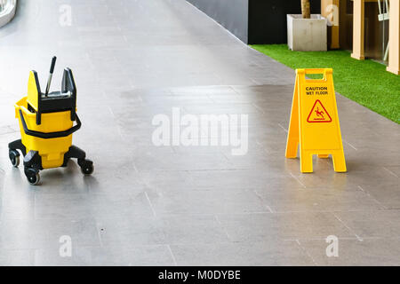 yellow sign inside building hallway, Sign showing warning of caution wet floor, Selective focus - Stock Photo