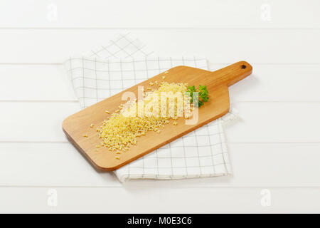 heap of uncooked alphabet pasta on wooden cutting board - Stock Photo