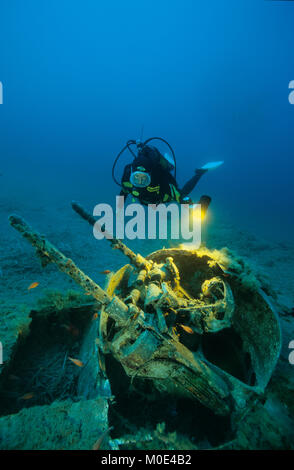 Scuba diver at anti-aircraft gun of a North American B-25 Mitchell bomber, crashed at 2nd world war, Aleria, Corse, - Stock Photo