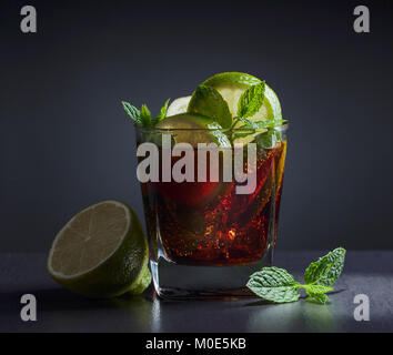 Cola with rum , lime  and mint on black table in bar. - Stock Photo