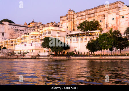 Udaipur city palace as seen from a boat on lake pichola at dusk with the purple gold tones. The sunset boat ride - Stock Photo