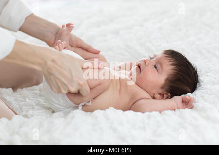 baby newborn is enjoying massage from mother - Stock Photo