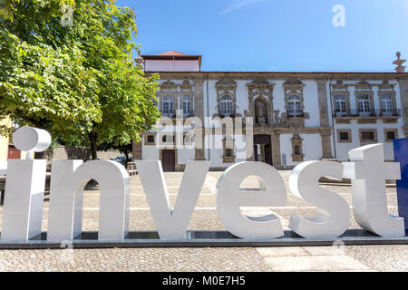 Word Invest created by big plastic letters in front of traditional architecture - Stock Photo