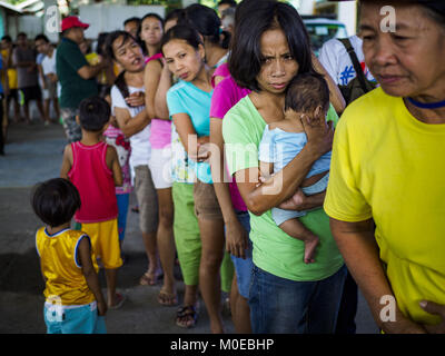 Camalig, Albay, Philippines. 21st Jan, 2018. People line up for relief supplies at the Barangay Cabangan evacuee - Stock Photo