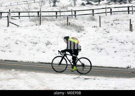 West Yorkshire, UK. 21st Jan, 2018. A man cycling up Blackstone Edge in snow, West Yorkshire, 20th January, 2018 - Stock Photo