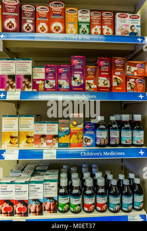 Cough medicines and childrens pain killers (analgesics) on a pharmacy  shelf in an English Pharmacy. - Stock Photo