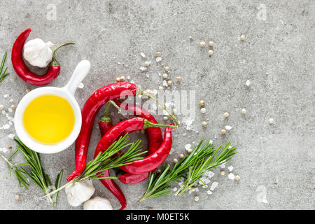 Culinary background a space for a text, flat lay composition of oil, chili peppers, rosemary, garlic and spices - Stock Photo