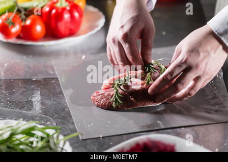 Rare lambs ready for marinade with rosemary. Cooking with fire in frying pan. Professional chef in a kitchen of - Stock Photo