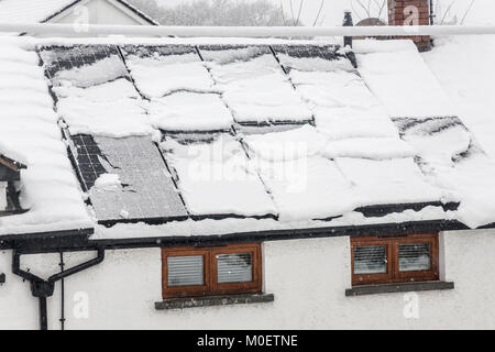 Solar panels on house covered in snow about to slide off, Llanfoist, Abergavenny, Wales, UK - Stock Photo