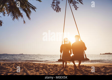 romantic couple in love sitting together on rope swing at sunset beach, silhouettes of young man and woman on holidays - Stock Photo