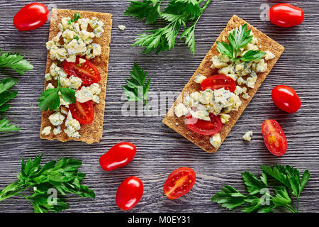 Crispbread with blue cheese and tomatoes - Stock Photo