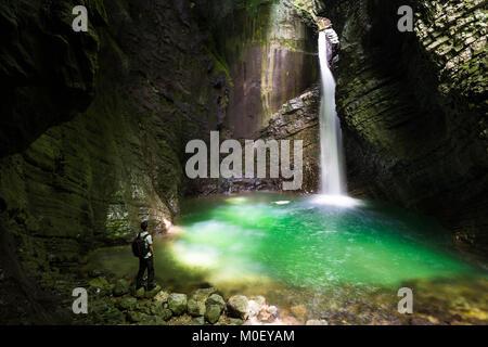 Man looking at waterfall, Kozjak, Slovenia - Stock Photo