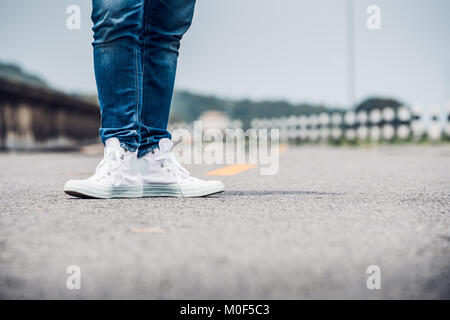Close up woman wear jean and white sneaker standing on highway road in sunny day,Alone travel or solo traveler concept. - Stock Photo