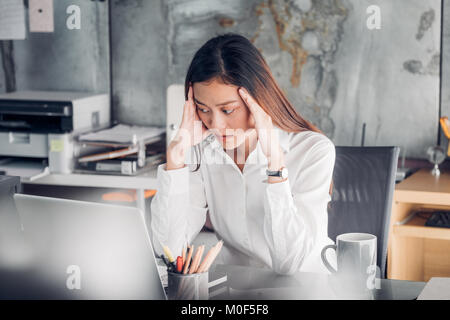 Frustrated Asian businesswoman cover her face with two hand and feel upset from work in front of laptop computer - Stock Photo