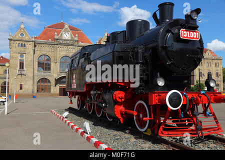 Arad, town in Crisana region of Romania. Old train station with vintage obsolete black steam engine locomotive. - Stock Photo
