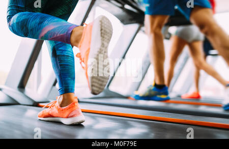 Group of friends exercising on treadmill machine - Stock Photo