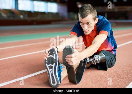 Handicapped Sportsman Stretching in Stadium - Stock Photo