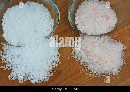 Himalayan and sea salt on wooden background - Stock Photo
