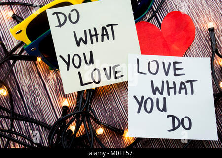 do what you love, love what you do - motivational word advice or reminder on sticky notes on cork board background - Stock Photo