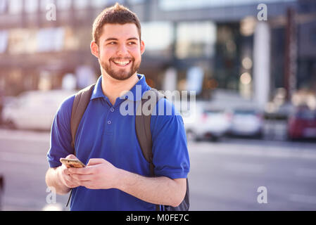 Young man using his phone for directions - Stock Photo