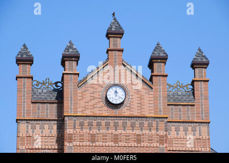 Poltavskaya, Russia - April 07, 2016: Clock on the wall of a brick building. Brown brick building with boshni and - Stock Photo