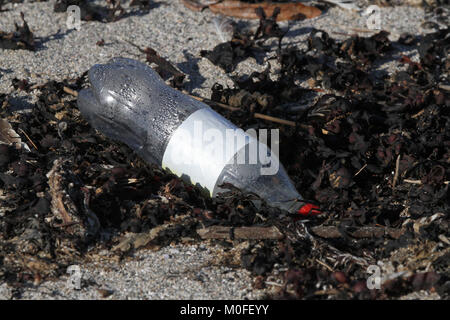 Plastic soft drink bottle on beach. - Stock Photo