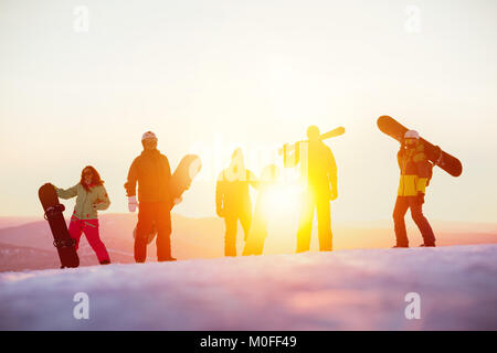 Group of serious friends with ski and snowboards against sunset - Stock Photo