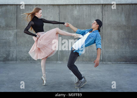 A young couple in love passionately dances on a city street. Ballerina and athlete parkour. Meshenie classical and - Stock Photo