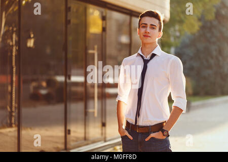 Stylish guy a teenager in a white shirt and tie is standing on the mall near the store. - Stock Photo