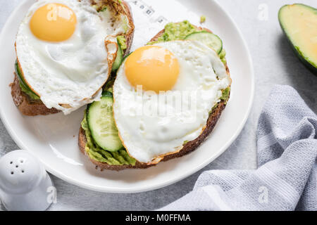 Egg and avocado breakfast toast on white plate. Closeup view. Healthy eating dieting concept - Stock Photo