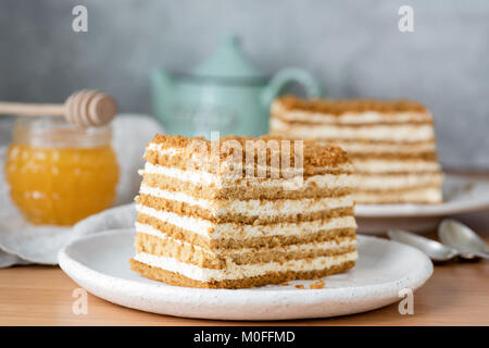 Honey layered cake or russian cake Medovik on white plate. Closeup view, selective focus - Stock Photo