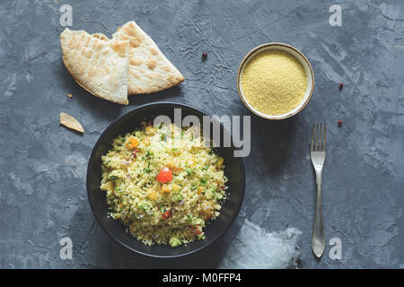 Tabbouleh with cous cous and arabic flatbread on concrete background. Healthy dietetic meal. Table top view - Stock Photo