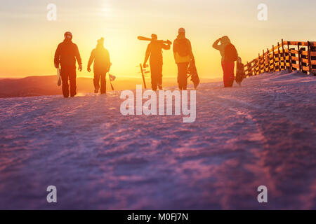 Friends with ski and snowboards walking to sunset - Stock Photo