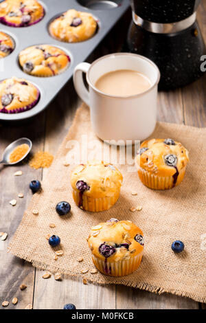 Freshly baked blueberry muffins with almond, oats and icing sugar topping on a rustic wooden table and a mug of - Stock Photo