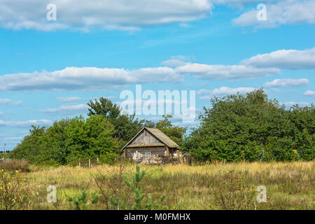 Rural landscape. Freestanding wooden rustic house among trees in Sunny weather - Stock Photo