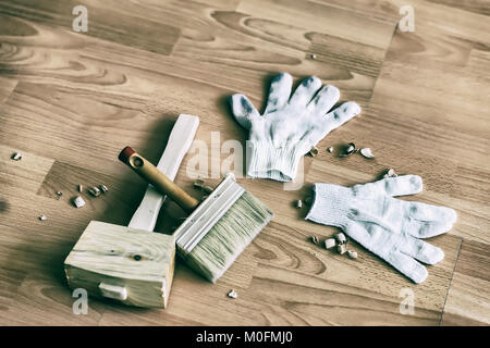 Set of hammer, gloves, brush left by on floor, toned image. Concept of handmade, professionalism and hobby - Stock Photo