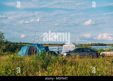 The tourist camp of tents on a river in summer Sunny weather. The horizontal frame. - Stock Photo
