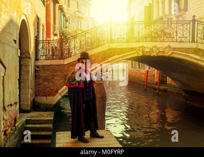 Unidentified man in black costume, hat and mask posing in front of small Venetian bridge over narrow canal during - Stock Photo