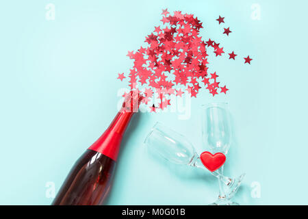 Confetti in the shape of red stars poured out of bottle champagne on the blue background. Top view. Concept. - Stock Photo