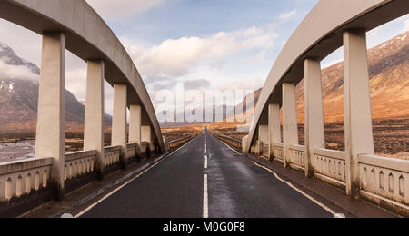 The A82 crosses a early-20th century concrete bridge over the River Etive, a mountain stream in the wilderness landscape - Stock Photo