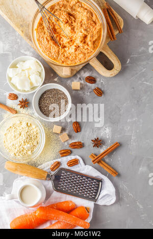 Healthy baking of carrot cake, vegan dessert ingredients: dough in a bowl, chia, coconut butter, almond milk, nuts. - Stock Photo