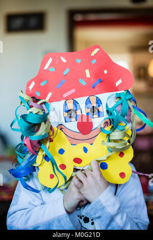 portrait of a 6 year old boy with a carnival mask made by himself at home - Stock Photo
