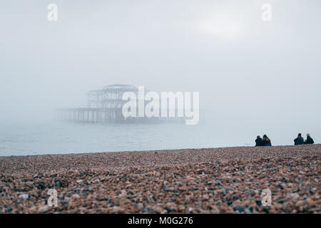 People sitting on the beach looking at West Pier in Brighton, the most popular seaside destination in the UK for - Stock Photo