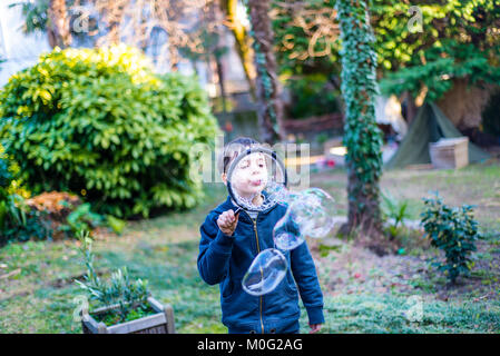 7-year-old child outdoors in the garden in winter makes big soap bubbles - Stock Photo